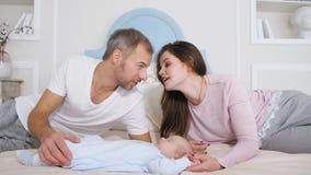 Aantrekkelijke man en vrouw die zoete slaapbaby bekijken in slaapkamer stock videobeelden