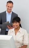 Aantrekkelijke manager die het werk van zijn werknemer controleert stock fotografie