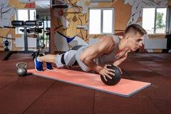 Aantrekkelijke Mannelijke de Geneeskundebal van Atletenperforming push-ups on royalty-vrije stock fotografie