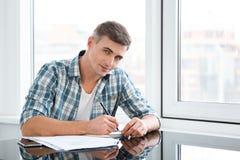 Aantrekkelijke mannelijke zitting en het werken in het bureau Stock Foto's