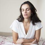 Aantrekkelijke medio volwassen vrouw met maagproblemen aangaande bed stock foto