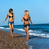 Aantrekkelijke meisjesvrienden die langs kust lopen. royalty-vrije stock foto's