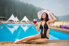Aantrekkelijke meisjeszitting naast zwembad met cocktail, die de zomer van vakantie op de achtergrond van machtig bos genieten stock afbeeldingen