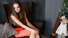 Aantrekkelijke meisjeszitting op bruine comfortabele stoel in Kerstmisbinnenland stock videobeelden