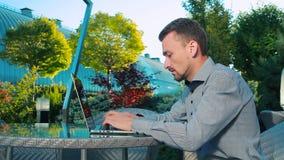 Aantrekkelijke mens die buiten aan laptop werken stock footage