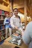 Aantrekkelijke mens die een boek overhandigen aan de vrouwelijke bibliothecaris stock afbeeldingen