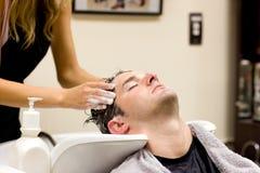Aantrekkelijke mens die een shampoo heeft stock fotografie