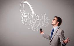 Aantrekkelijke mens die en aan muziek met abstract hoofd zingen luisteren Royalty-vrije Stock Foto