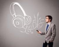 Aantrekkelijke mens die en aan muziek met abstract hoofd zingen luisteren Stock Fotografie
