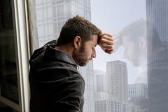Aantrekkelijke mens die op bedrijfsdistrictsvenster leunen die aan emotionele crisis en depressie lijden Stock Foto's