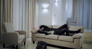 Aantrekkelijke mens die uit het werk thuis zeer het gelukkige en charismatische springen over de bank in een grote ruime woonkame stock videobeelden