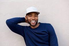 Aantrekkelijke mens die zich met hand achter hoofd bevinden en door muur glimlachen royalty-vrije stock afbeeldingen