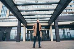 Aantrekkelijke mens in het in bruine laag stellen dichtbij commercieel centrum De knappe Europese mens met baard kijkt weg Concep stock afbeeldingen