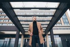 Aantrekkelijke mens in het in bruine laag stellen dichtbij commercieel centrum De knappe Europese mens met baard kijkt weg Concep royalty-vrije stock fotografie