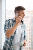 Aantrekkelijke mens het drinken koffie en het spreken op cellphone Stock Foto
