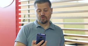 Aantrekkelijke mens met een baard die op een mobiele telefoon spreken stock video