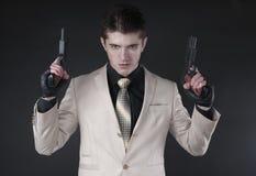 Aantrekkelijke mens met een kanon die een wit kostuum dragen Stock Fotografie