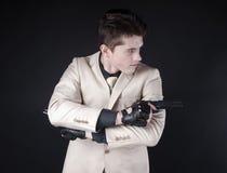 Aantrekkelijke mens met een kanon die een wit kostuum dragen Stock Afbeelding