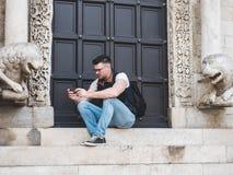 Aantrekkelijke mens met een telefoon, die op de straat zitten stock afbeelding