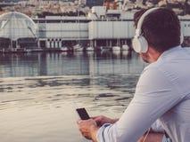Aantrekkelijke mens met hoofdtelefoons en een telefoon, die op het strand zitten stock foto