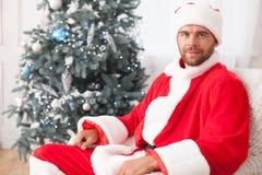 Aantrekkelijke mens in rood kostuum dichtbij Kerstboom stock afbeeldingen