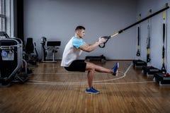 Aantrekkelijke mens tijdens training met opschortingsriemen in de Gymnastiek royalty-vrije stock afbeeldingen