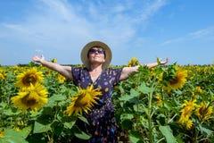 Aantrekkelijke middenleeftijdsvrouw in strohoed met wapens uitgestrekt op zonnebloemgebied, het vieren vrijheid Het positieve emo Royalty-vrije Stock Foto