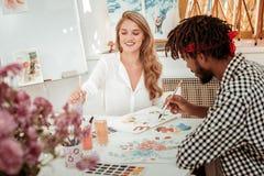 Aantrekkelijke modieuze kunstleraar die het blije schilderen met haar student voelen royalty-vrije stock fotografie