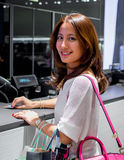 Aantrekkelijke, modieuze, modieuze jonge Aziatische vrouw die en bij de teller van de kassier winkelen betalen Stock Afbeelding
