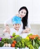 Aantrekkelijke moeder en zoon die een salade voorbereiden Royalty-vrije Stock Afbeelding