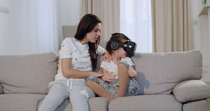 Aantrekkelijke moeder met haar dochter die een goede tijd doorbrengen samen aan de bank, bekijkt zij haar dochter hoe zij stock videobeelden