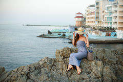 Aantrekkelijke mooie vrouw die met witte strohoed weg op zee en zonsondergang of zonsopgang kijken Wijfje met de zomerstrand Royalty-vrije Stock Foto's