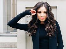 Aantrekkelijke mooie vrouw met pluizige donkerbruine lange haren, die op de grijze muur stellen, die zwarte uitrusting dragen De  Royalty-vrije Stock Foto's