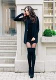 Aantrekkelijke mooie vrouw met pluizige donkerbruine lange haren, die op de grijze muur stellen, die zwarte uitrusting en hoog zw Stock Foto