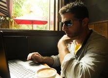 Aantrekkelijke nadenkende en peinzende millennial mens die van Internet-koffiewinkel werken met laptop computer denken die die wo royalty-vrije stock foto