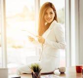 Aantrekkelijke onderneemster die een digitale tablet voor het bureau van ochtendvensters gebruiken royalty-vrije stock afbeelding