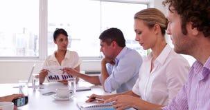 Aantrekkelijke onderneemster die een grafiek voorleggen aan commercieel team stock videobeelden