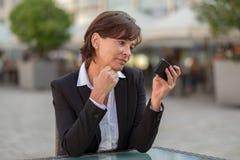 Aantrekkelijke onderneemster die een tekstbericht lezen Stock Foto's