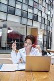 Aantrekkelijke onderneemster die met laptop bij koffie werken stock foto