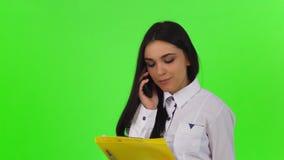 Aantrekkelijke onderneemster die op de telefoon spreken, die klembord houden stock footage