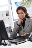Aantrekkelijke onderneemsterzitting bij bureau in bureau Stock Fotografie