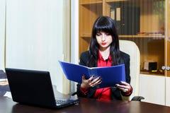 Aantrekkelijke onderneemsterzitting bij werkplaats in het bureau, rea Stock Afbeeldingen
