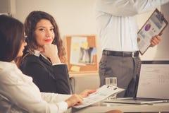 Aantrekkelijke onderneemsterzitting in het bureau, bij het bureau Aantrekkelijke Onderneemster Stock Afbeeldingen