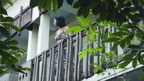 Aantrekkelijke op het balkon uitgaan en vrouw die rond kijken stock videobeelden