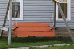 Aantrekkelijke oranje familieschommeling Stock Foto's