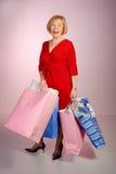Aantrekkelijke oudere dameholding het winkelen zakken stock foto's