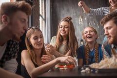 Aantrekkelijke popcorn werpen en jongeren die samen van genieten Stock Afbeeldingen
