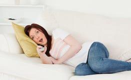 Aantrekkelijke roodharige vrouw die op TV let Royalty-vrije Stock Afbeeldingen