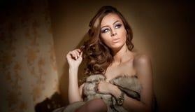 Aantrekkelijke sexy jonge die vrouw in een bontjaszitting wordt verpakt in hotelruimte Portret van sensueel vrouwelijk dagdromen  Royalty-vrije Stock Afbeeldingen