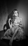 Aantrekkelijke sexy jonge die vrouw in een bontjaszitting wordt verpakt in hotelruimte Zwart-wit portret van sensueel vrouwelijk  Stock Foto
